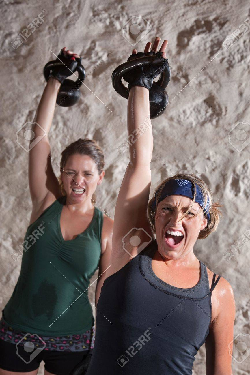 Instense women shout as they push kettle bell weights up Stock Photo - 15934502