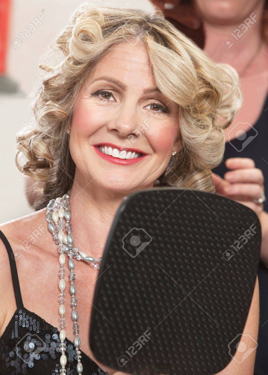 Attractive Middle Aged Female With Mirror In Hair Salon Stock Photo