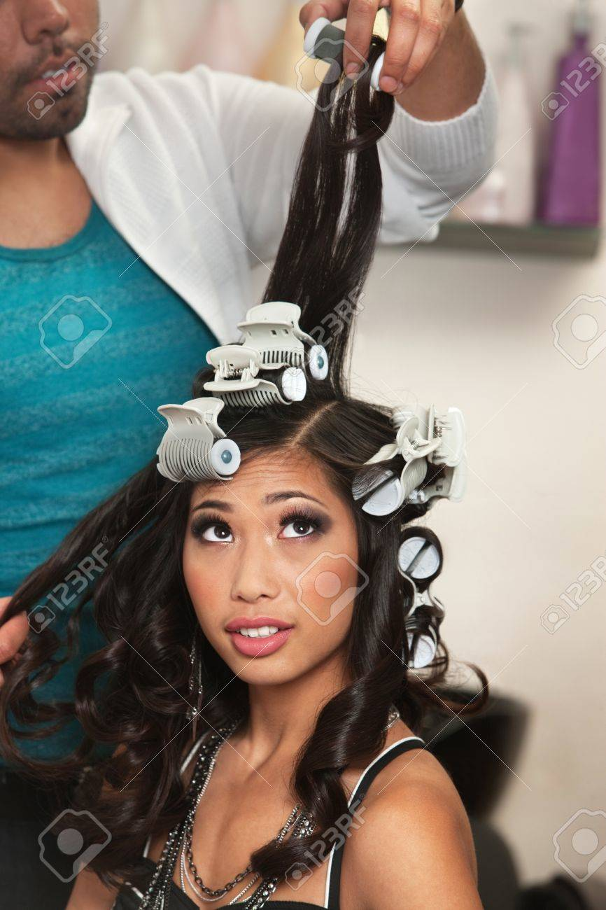 Pretty young woman watching curlers being removed from hair Stock Photo - 16578049