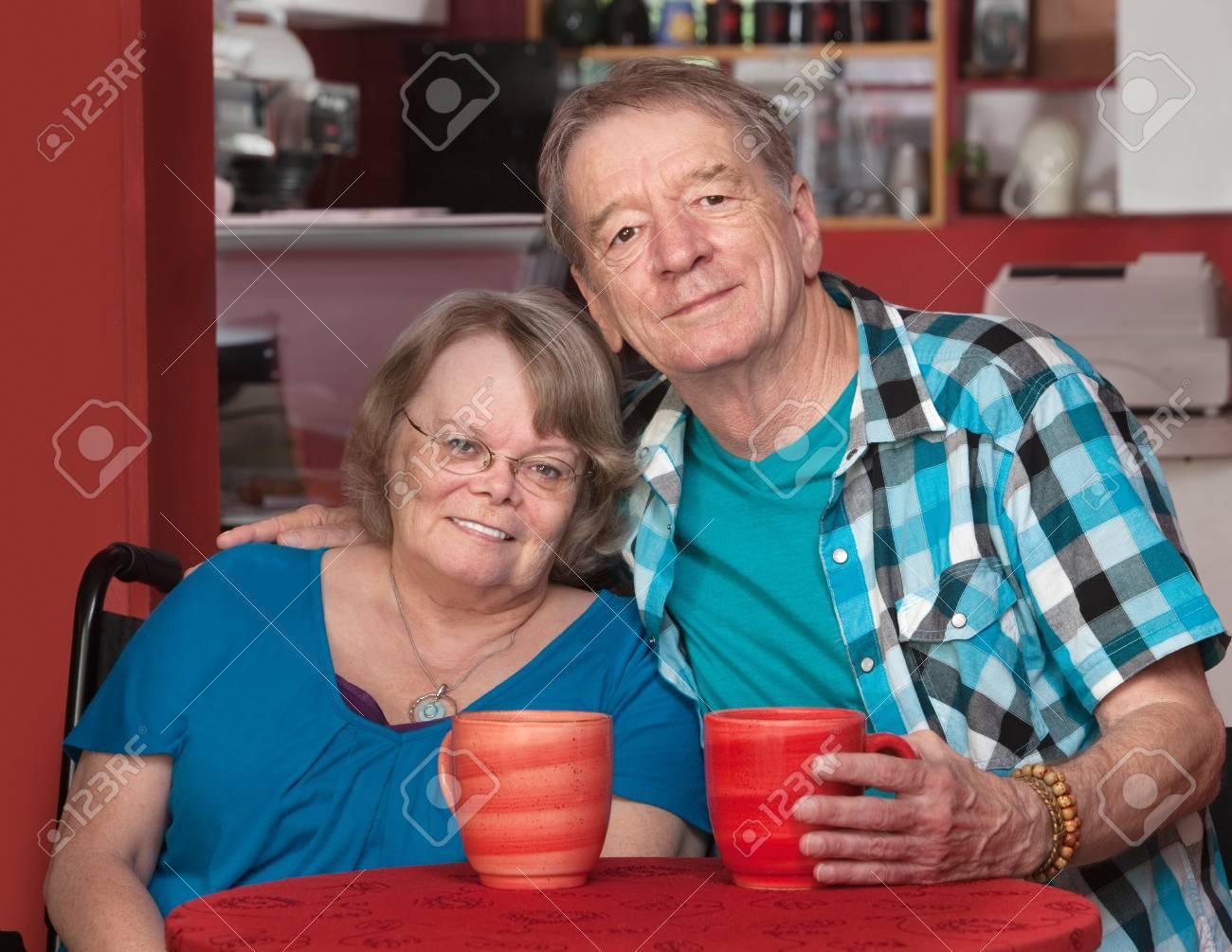 Joyful senior friends sitting with mugs at table Stock Photo - 17019815