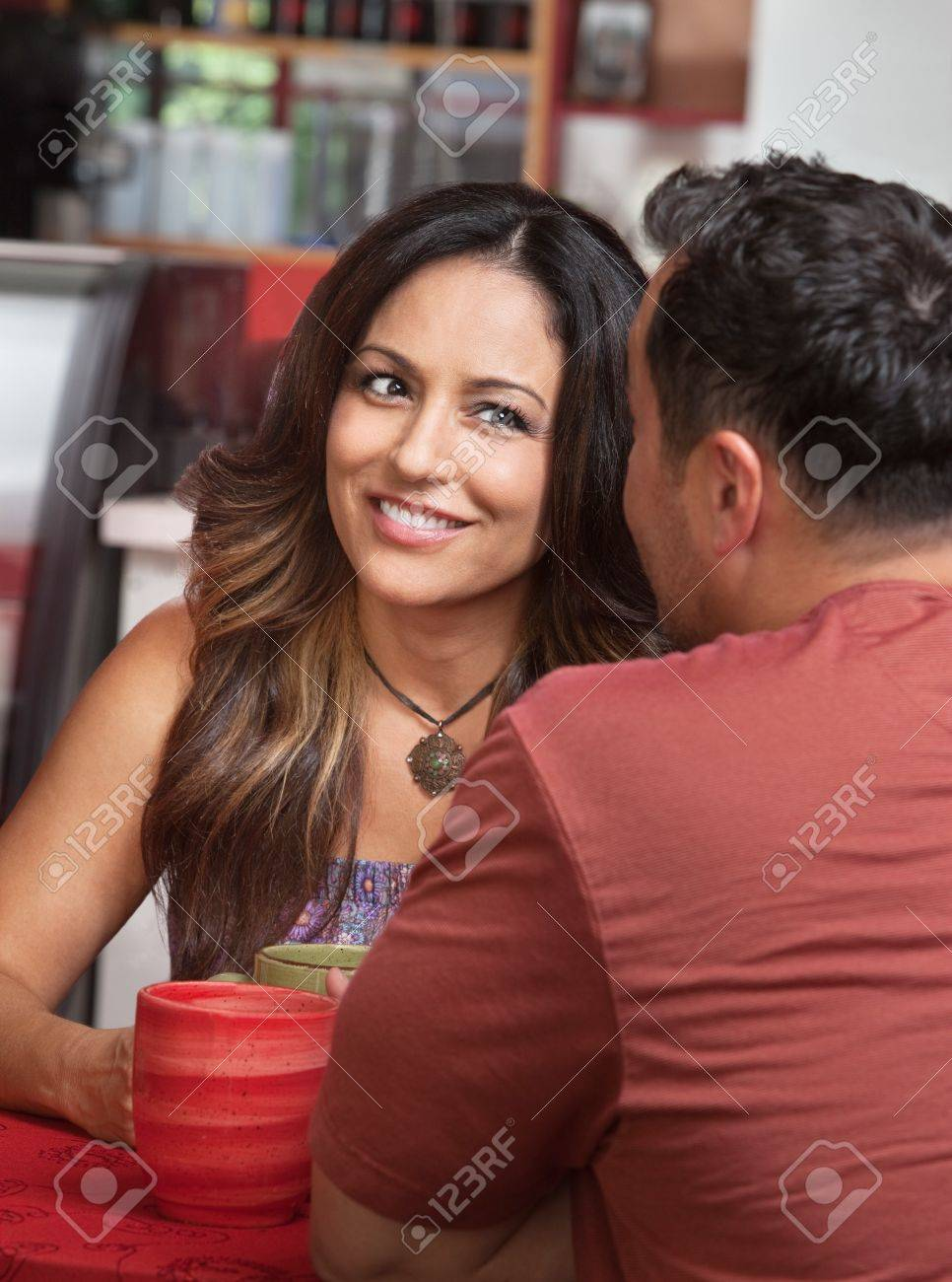 Skeptical Hispanic woman listening to man talk in cafe Stock Photo - 17019823