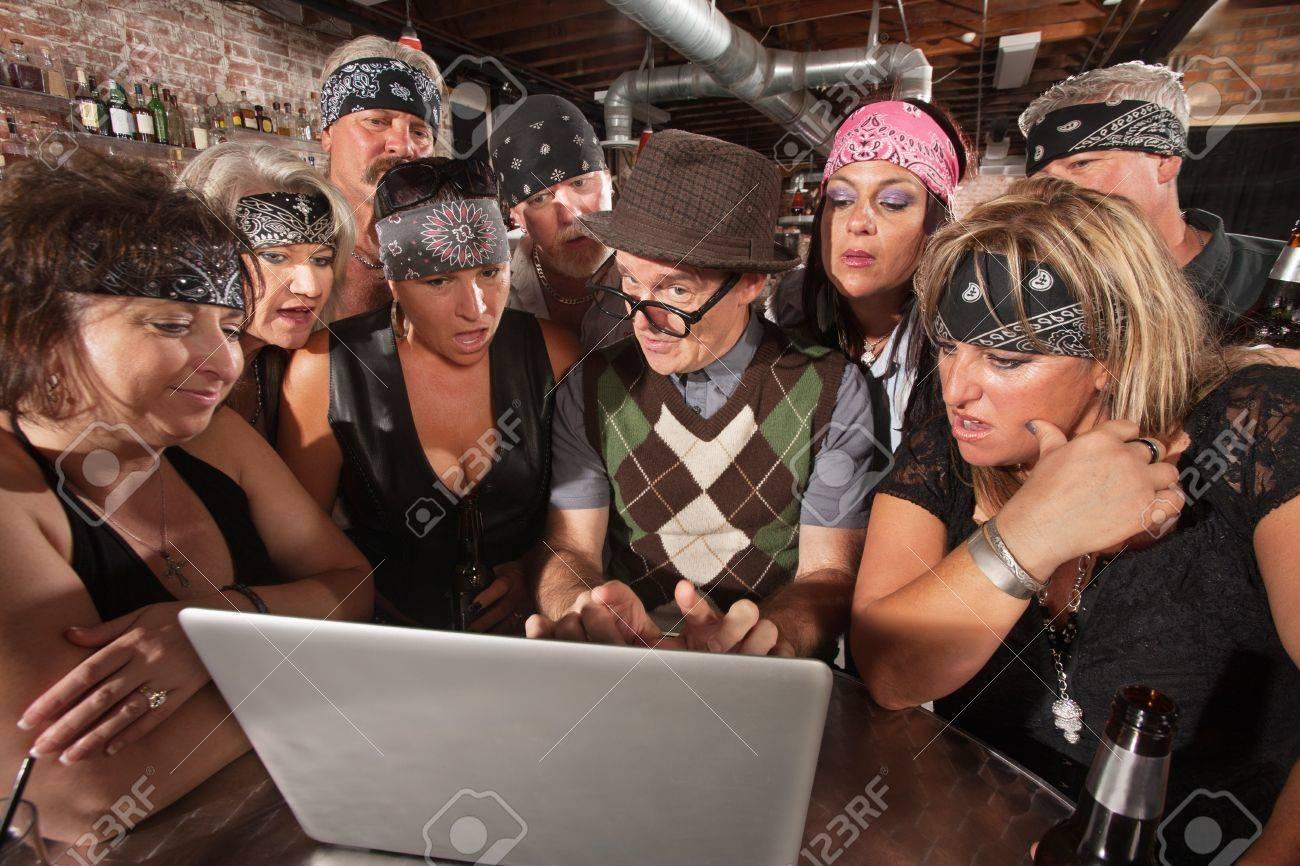 Group of impressed biker gang members watching nerd using a computer Stock Photo - 17544377