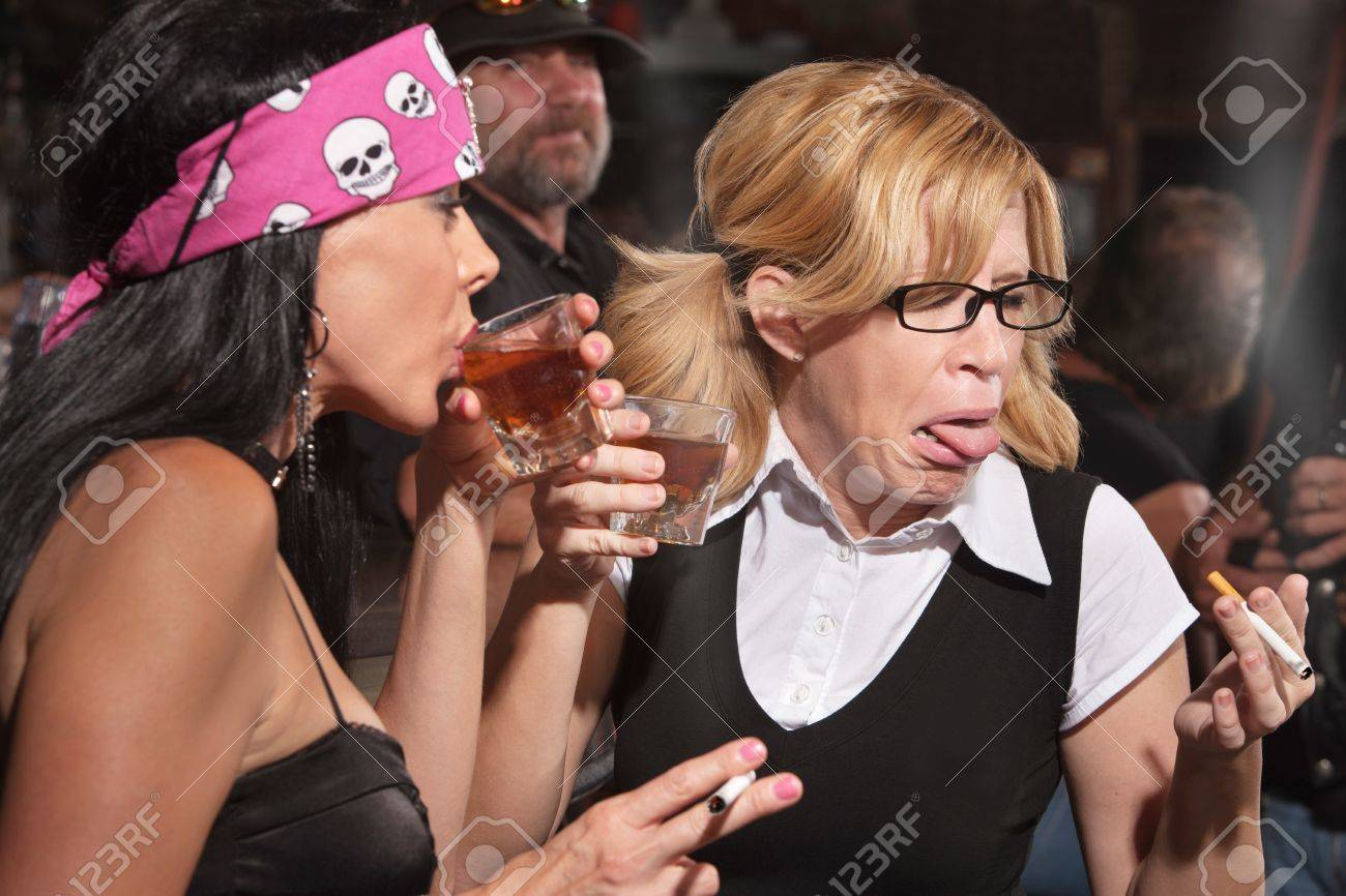 Female nerd sticking out tongue after tasting whiskey in bar Stock Photo - 17591137