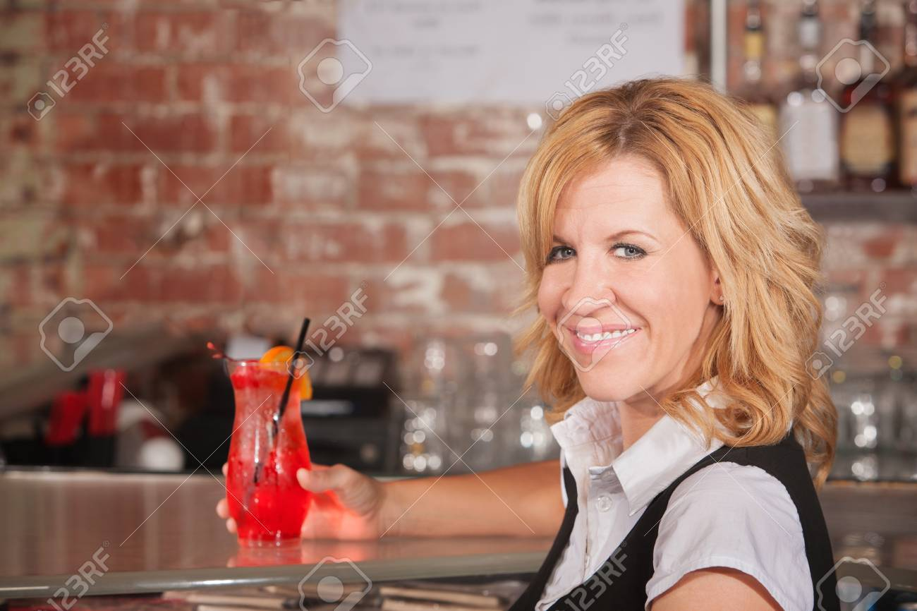 Happy hostess with alcoholic beverage glass in bar Stock Photo - 17591152