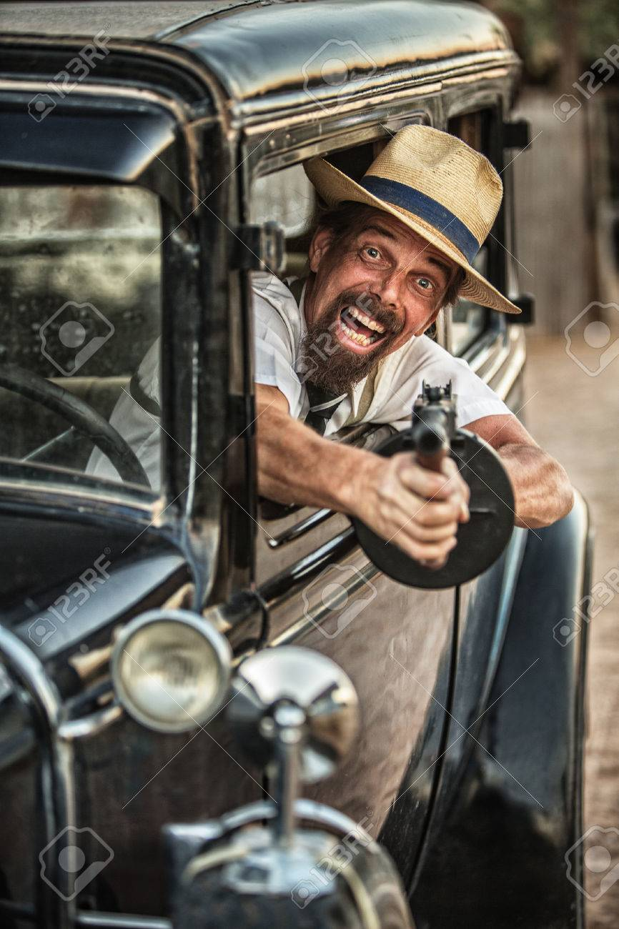 Man In Hat And Beard Shooting Gun From Old Car Stock Photo
