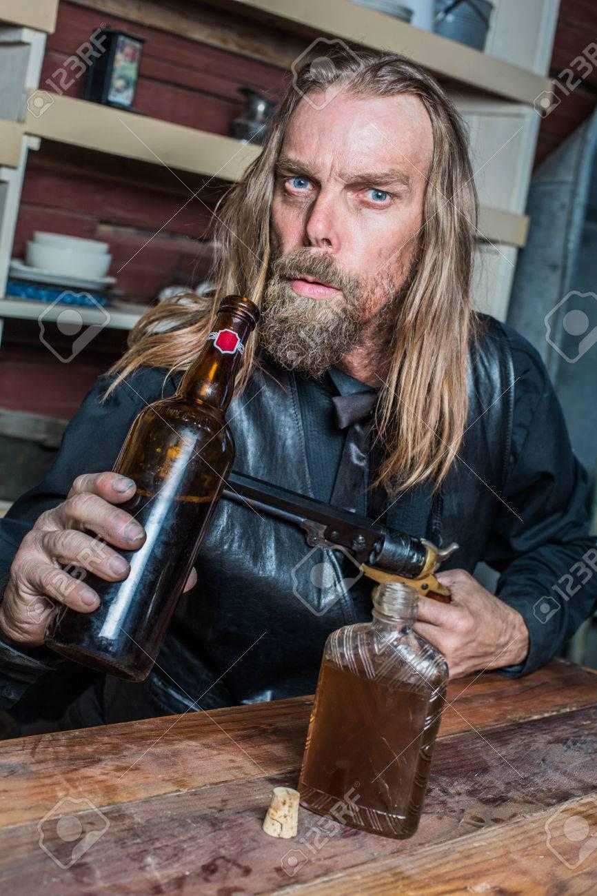 Drunk Man West Ziele Gun Gegen Flasche Während Er Am Tisch Sitzt