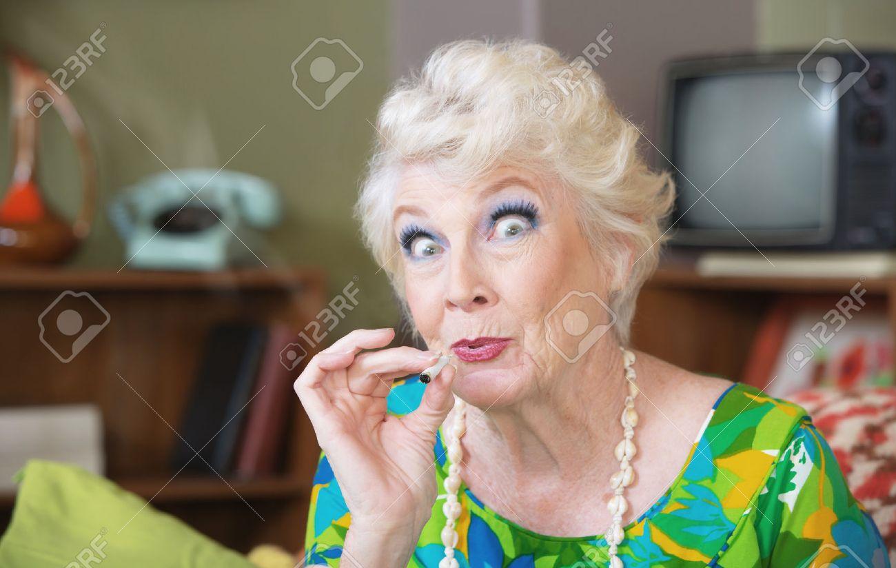Excited Caucasian senior woman in green smoking marijuana - 34079508