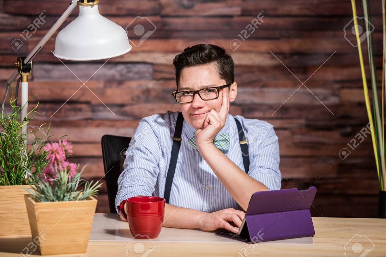 Wondering dapper female in suspenders at desk with grin