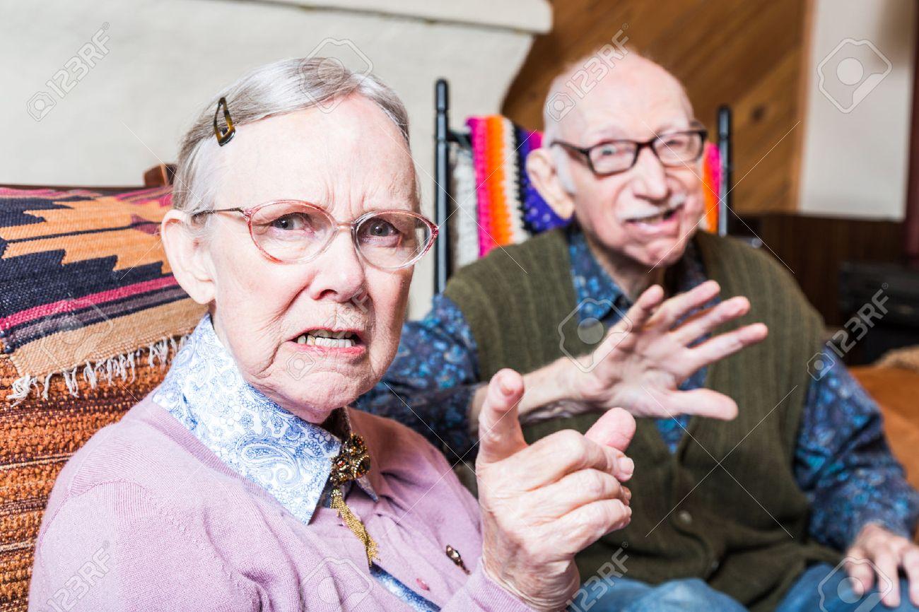 Verärgerter Alter Mann Und Frau Scowling Kamera Sitzt Im Wohnzimmer ...
