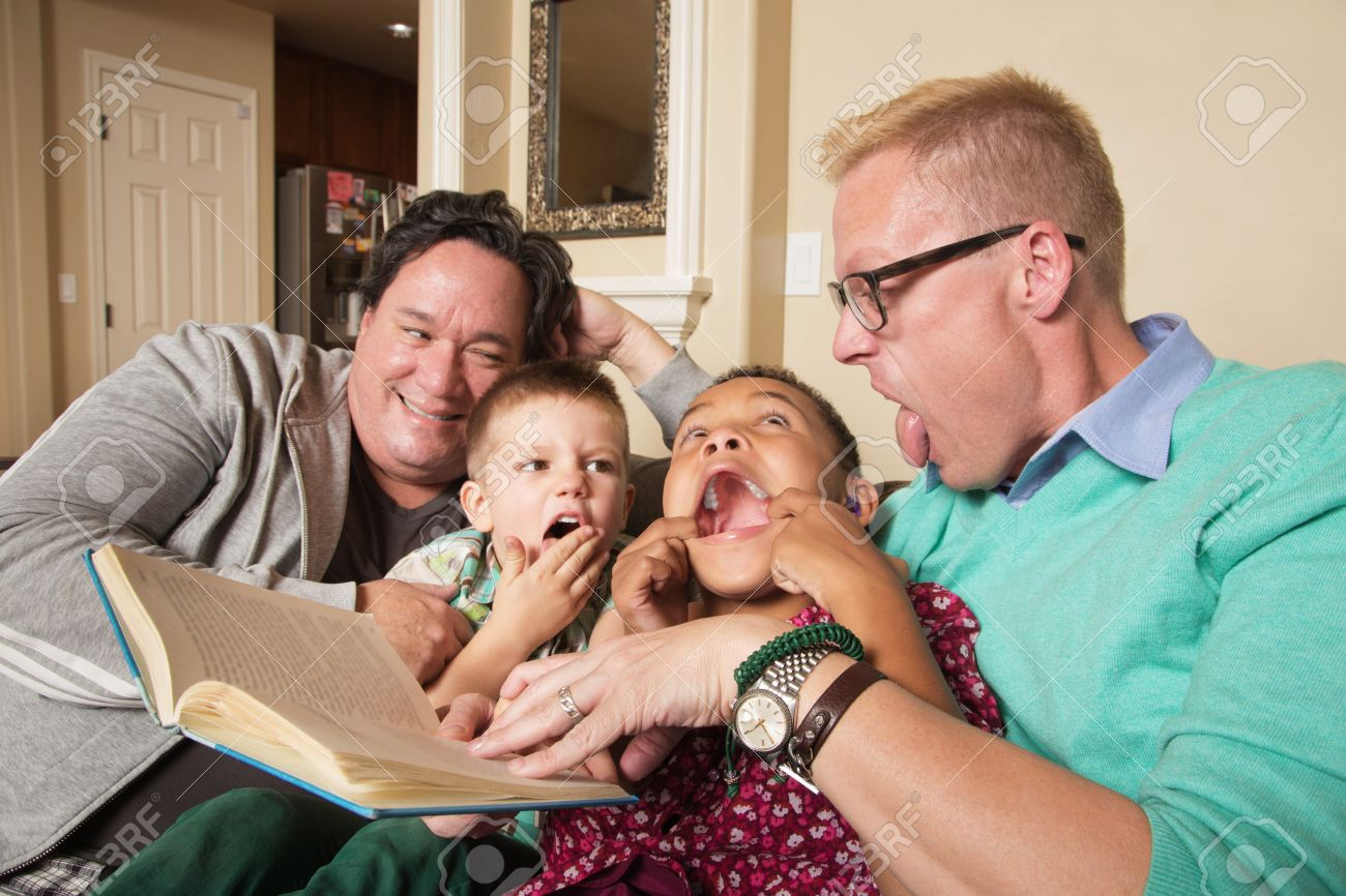Diverse same sex parents with children reading together Stock Photo -  48557366