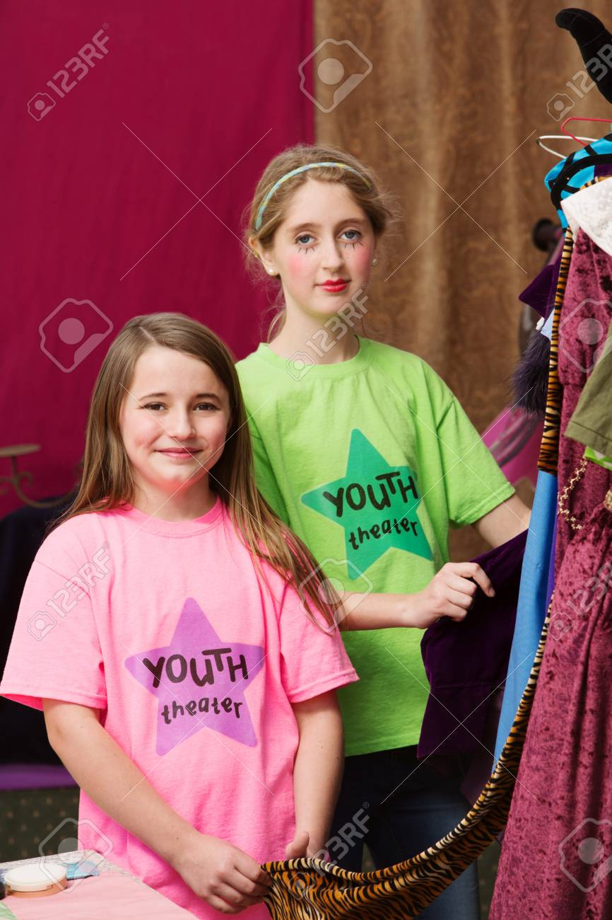 Two Girls Standing Near Costumes For A Youth Theater Program Stock