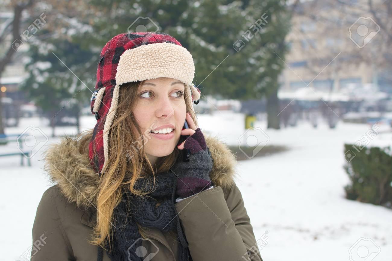 Foto de archivo - Niña con un sombrero de leñador hablando por su teléfono  celular en la nieve 43a46699c9c