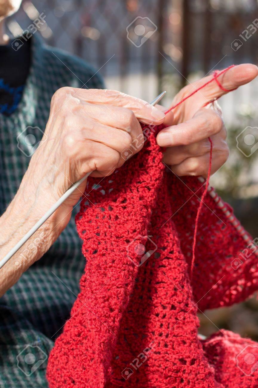 49f82dddc2a8 Senior femme, mains, tricoter avec de la laine rouge extérieur Banque  d images