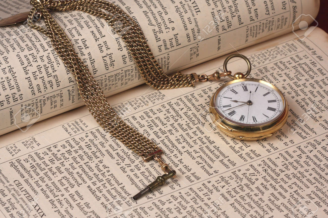 old gold pocket fobwatch on open pages of old bible stock photo