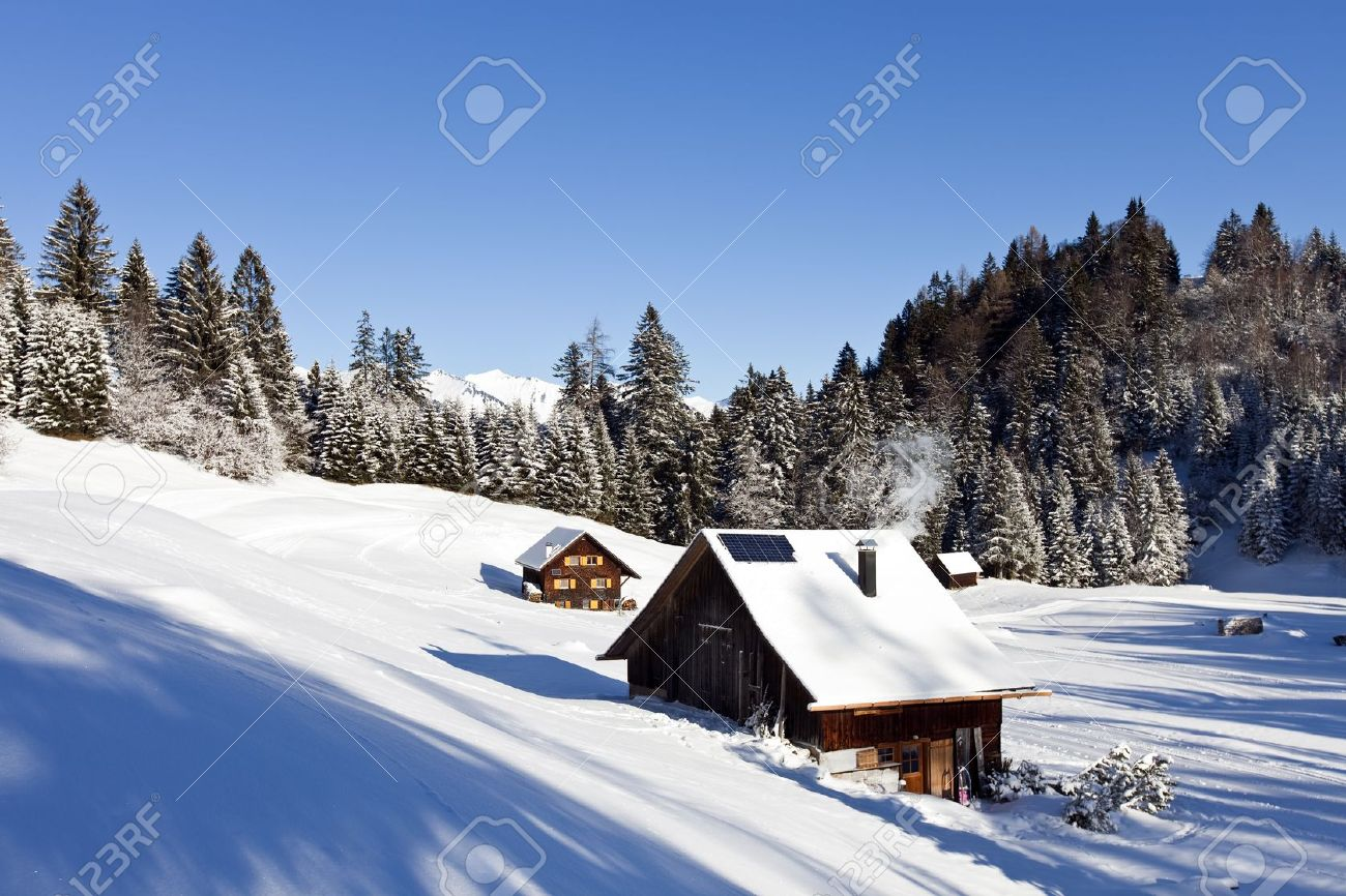 Very detailed photo of a sunny winter landscape with occupied and heated log cabins in the mountains and snowcovered mountaintops in the back Stock Photo - 22018593