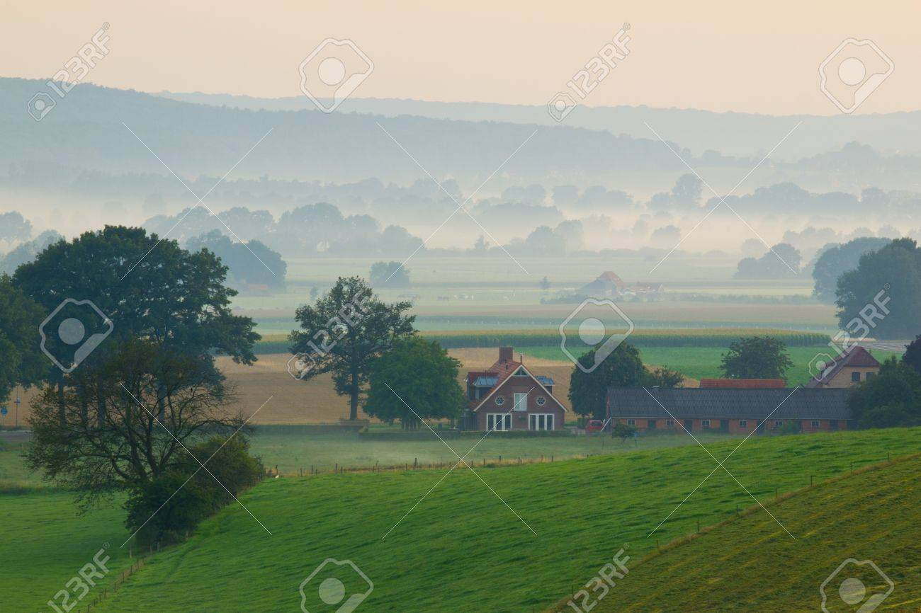 Sunrise over a misty farm in the hills Stock Photo - 10834511