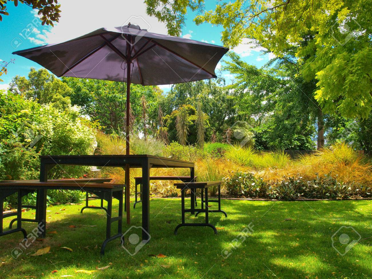 Dining Table With Chairs And Parasol In The Shade In A Lush Garden Stock  Photo