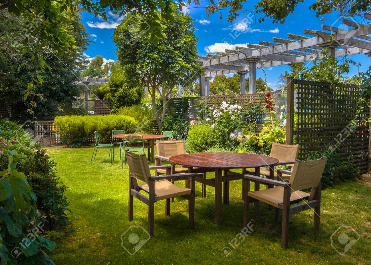 home backyard with garden table set in sunny a lush garden with