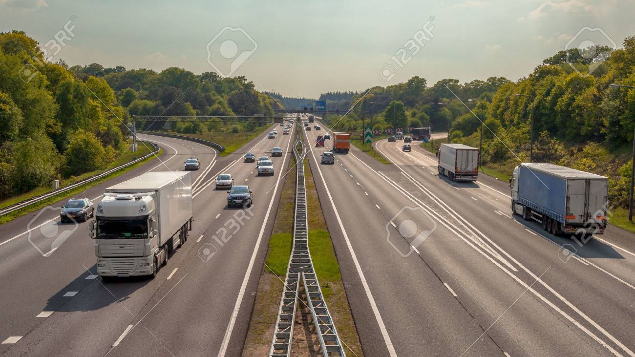 Right hand side Evening Traffic on the A12 Motorway through the Veluwe forest. One of the Bussiest highways in the Netherlands - 44290986