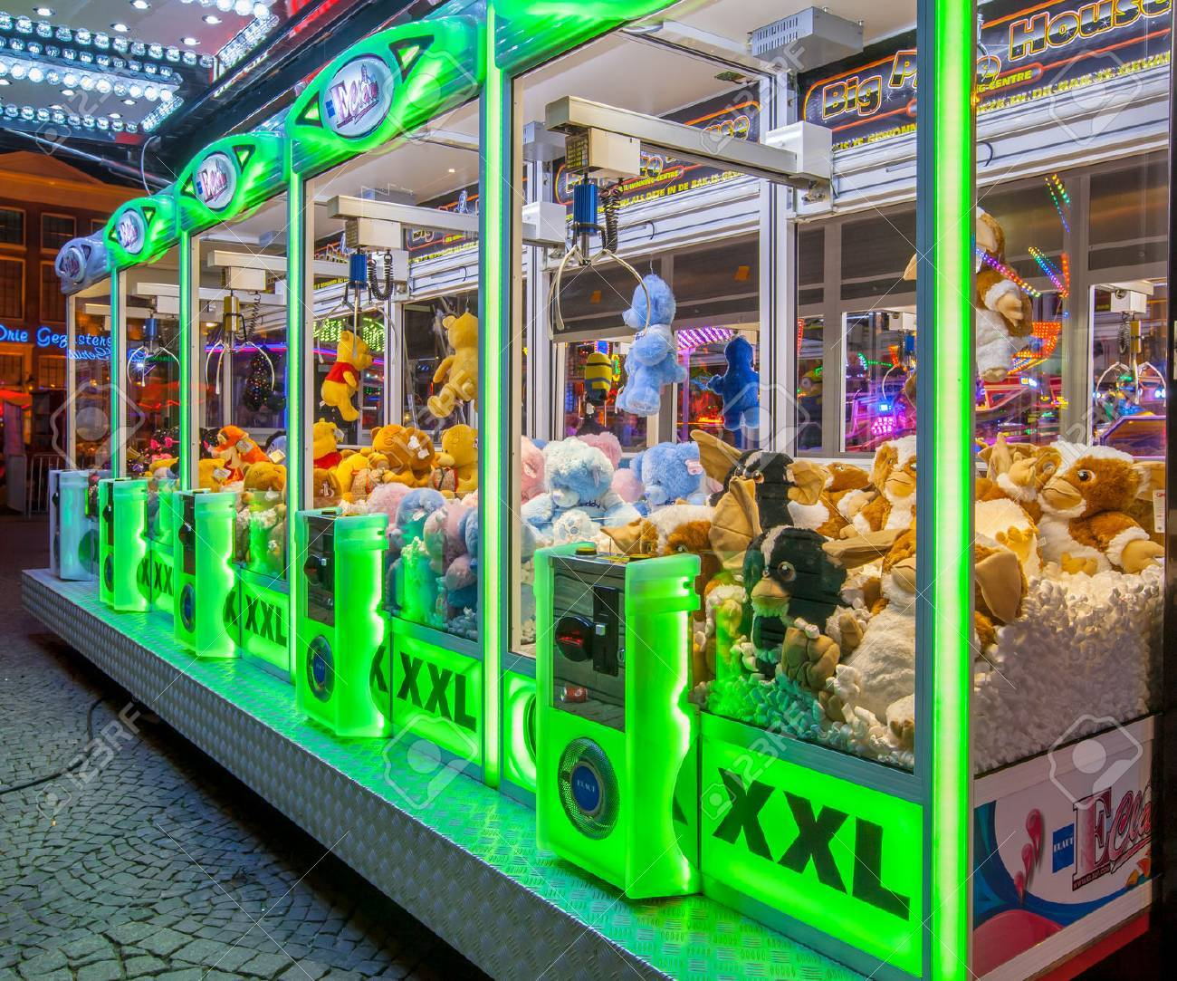 GRONINGEN, THE NETHERLANDS-MAY 5, 2015: Arcade crane vending machine with colourful green lights on the annual funfair on central square. - 53011976