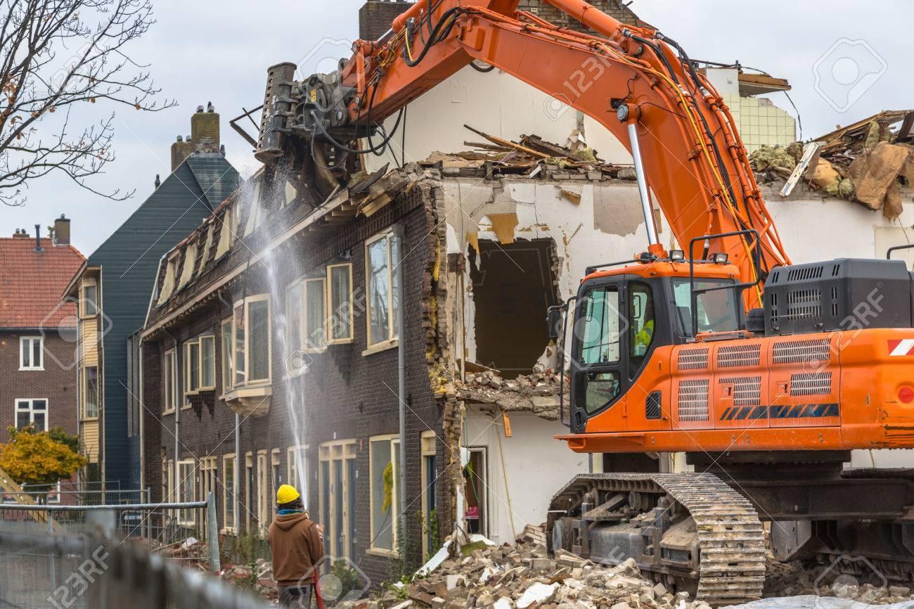 Orange Demolition crane demolishing old row of houses in the Netherlands - 84572478