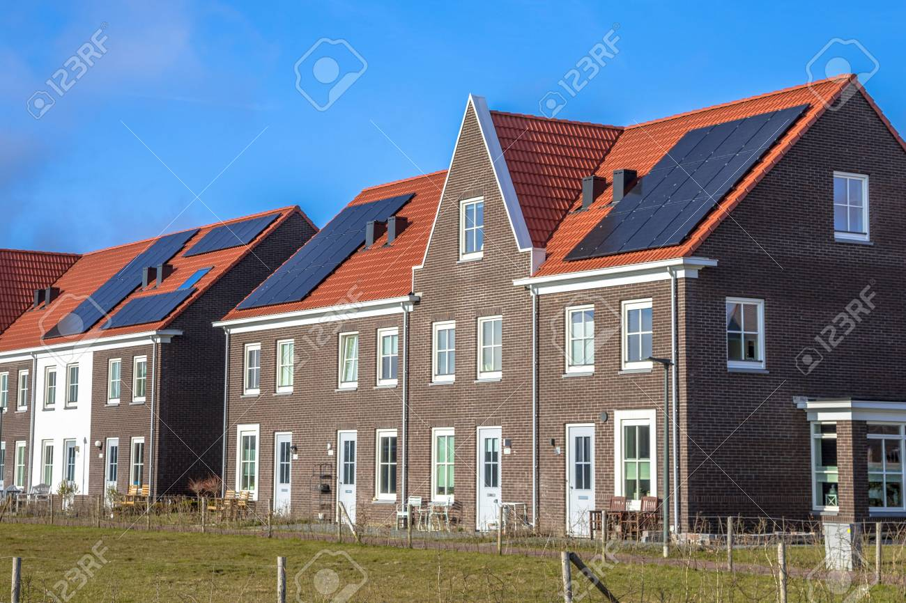 Modern row houses with solar panels, brown bricks and red roof tiles in neoclassical style in Groningen Netherlands on sunny day - 90752695