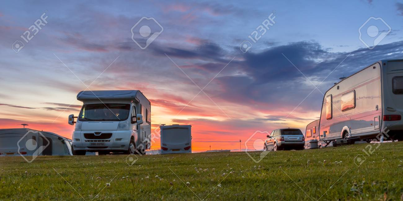 Camping caravans and cars parked on a grassy campground under beautiful sunset - 119682911