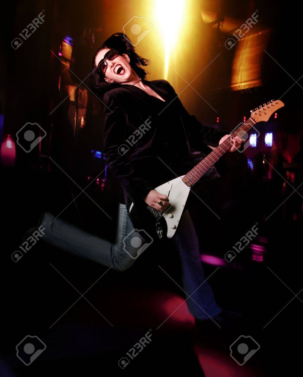 Female Lead Guitarist With Electric Guitar Jumping On Stage Stock Photo