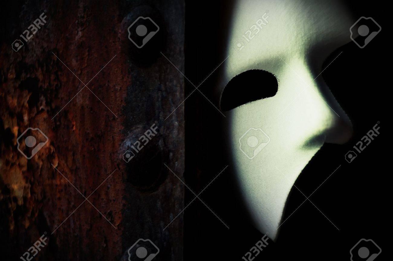 masquerade phantom of the opera mask on rusty bridge column stock