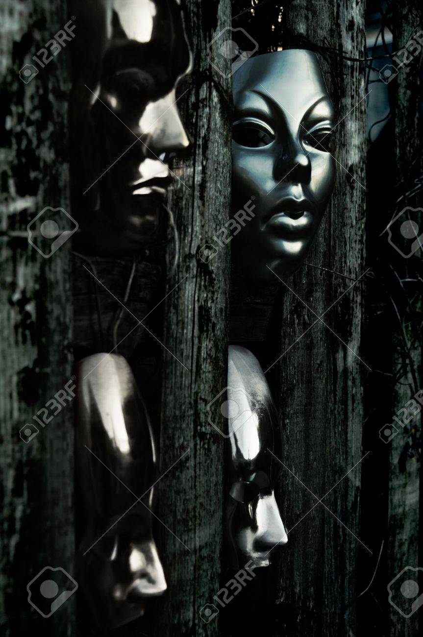 Trapped - Masks behind Weathered Fence Stock Photo - 15534869