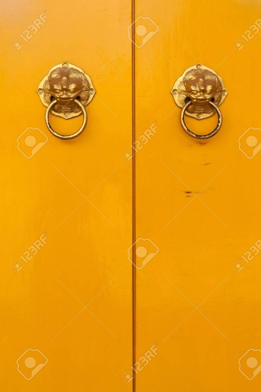 Golden chinese door handles on yellow doors in vertical - 10103835