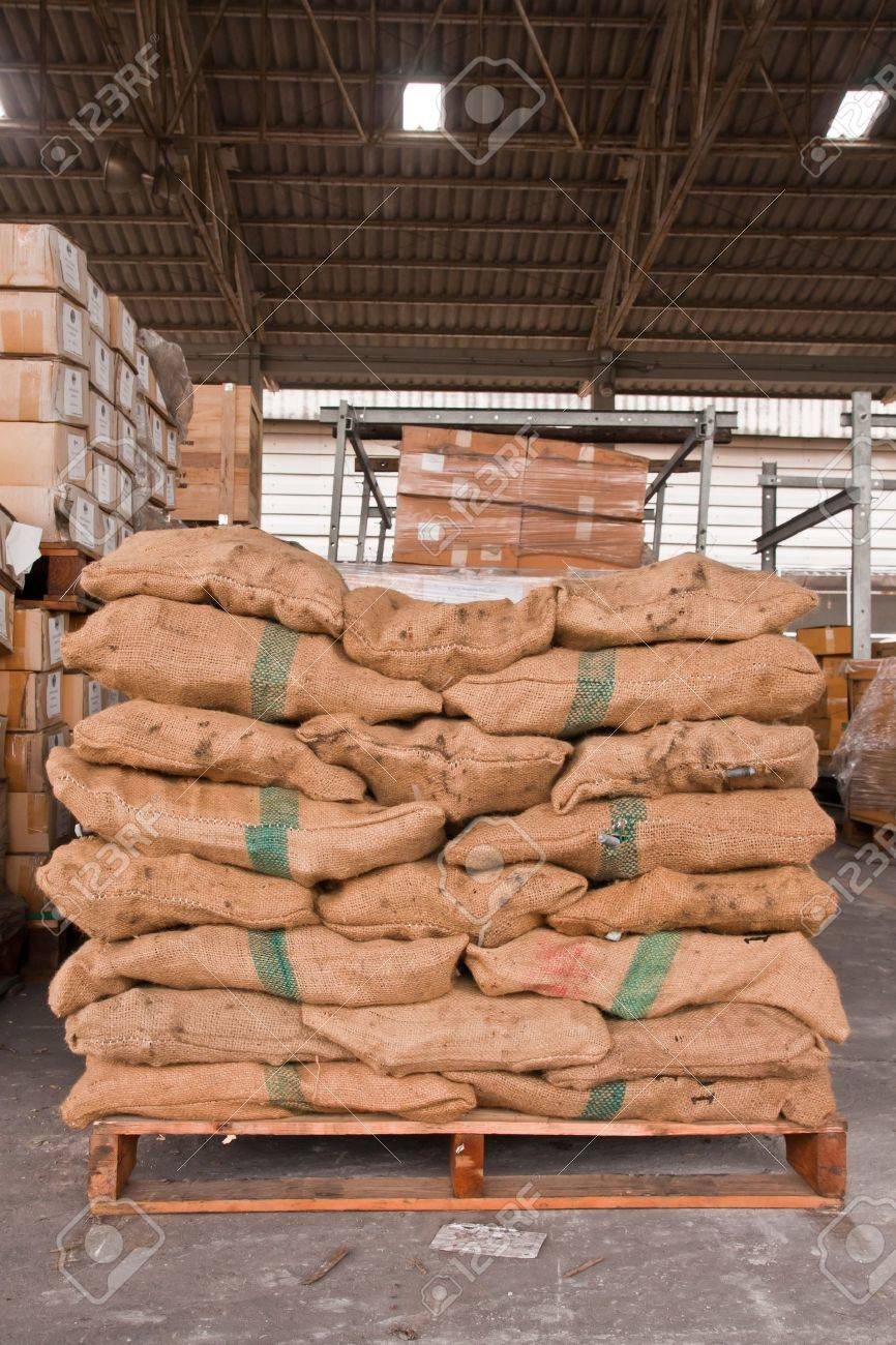 Brown sacks stack on wooden pallet in stockpile - 10463271