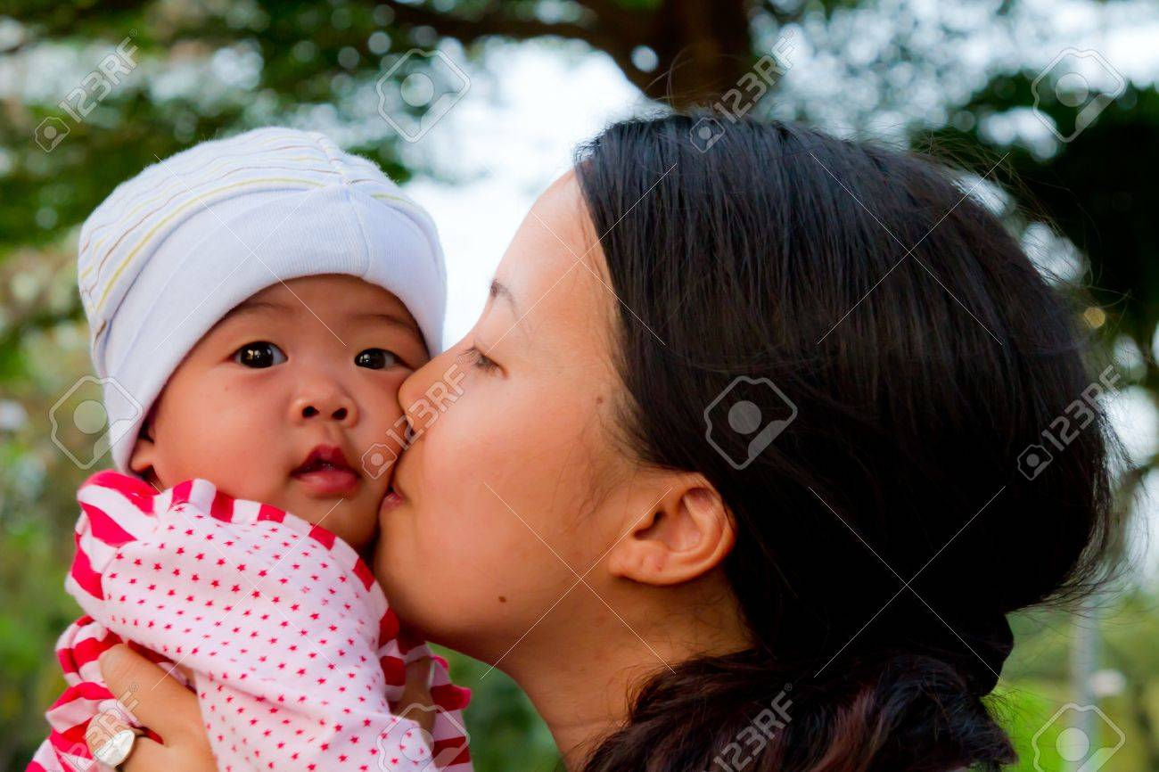 Asian woman kiss her baby daughter in park - 12640734