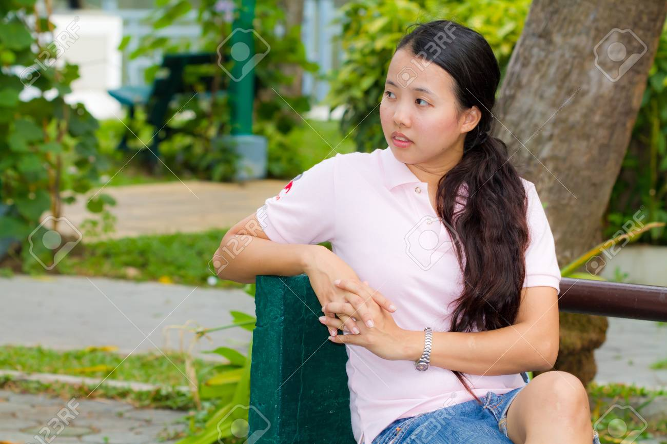 Distracted Asian woman on bench in park Stock Photo - 13102198