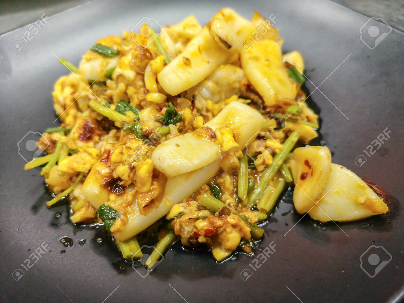 Thai cuisine stir squid in salted egg yolk sauce on black dish - 105929054