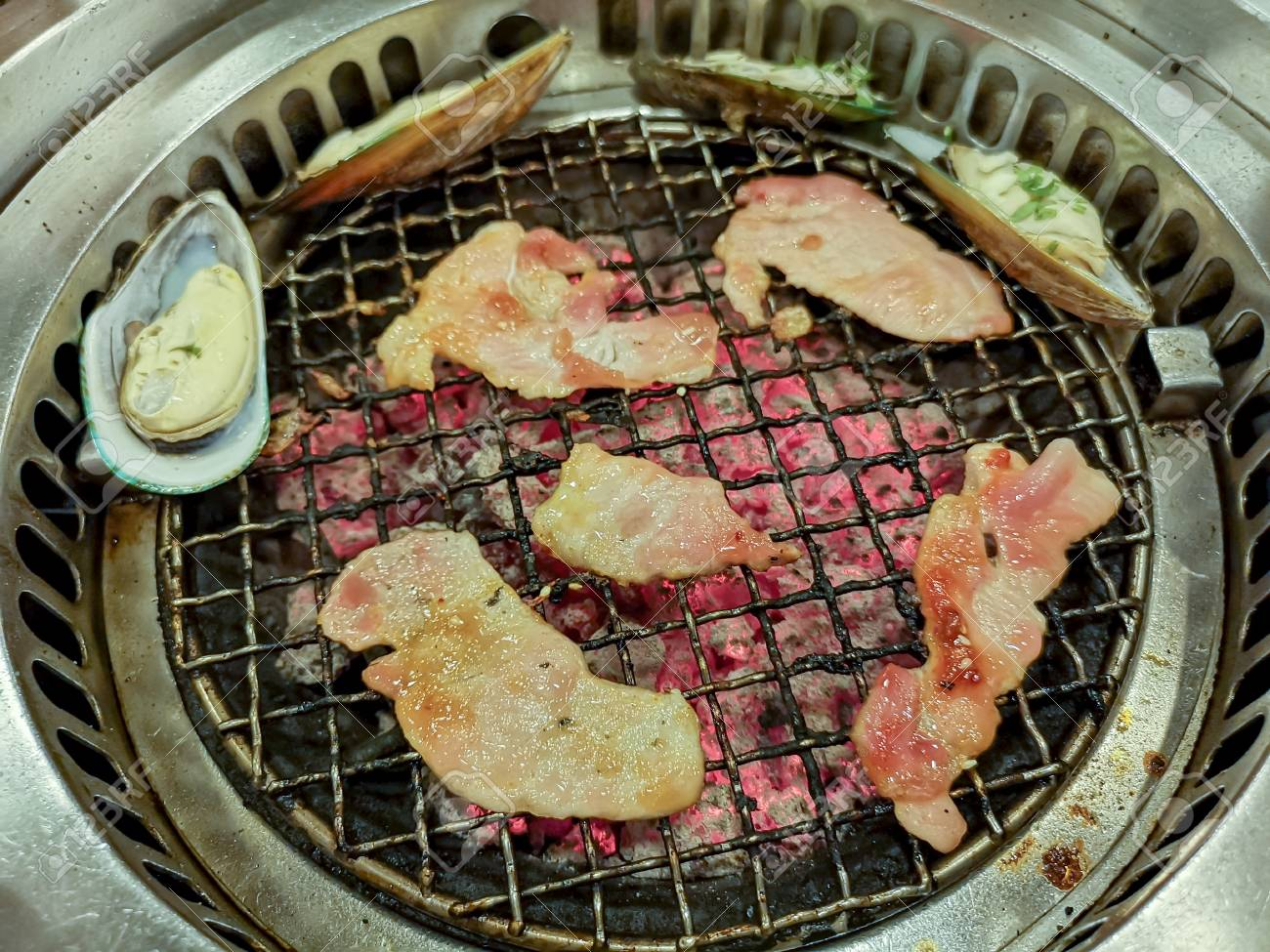 Cooking by grilling sliced pork on charcoal barbecue stove - 106054242