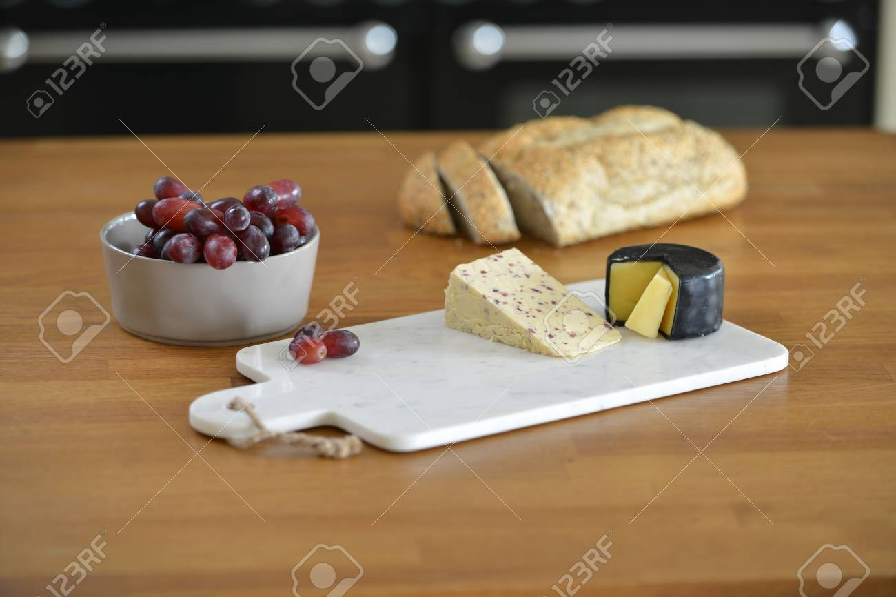 Stock Photo - White marble cheese board in a kitchen with cheese and grapes & White Marble Cheese Board In A Kitchen With Cheese And Grapes Stock ...