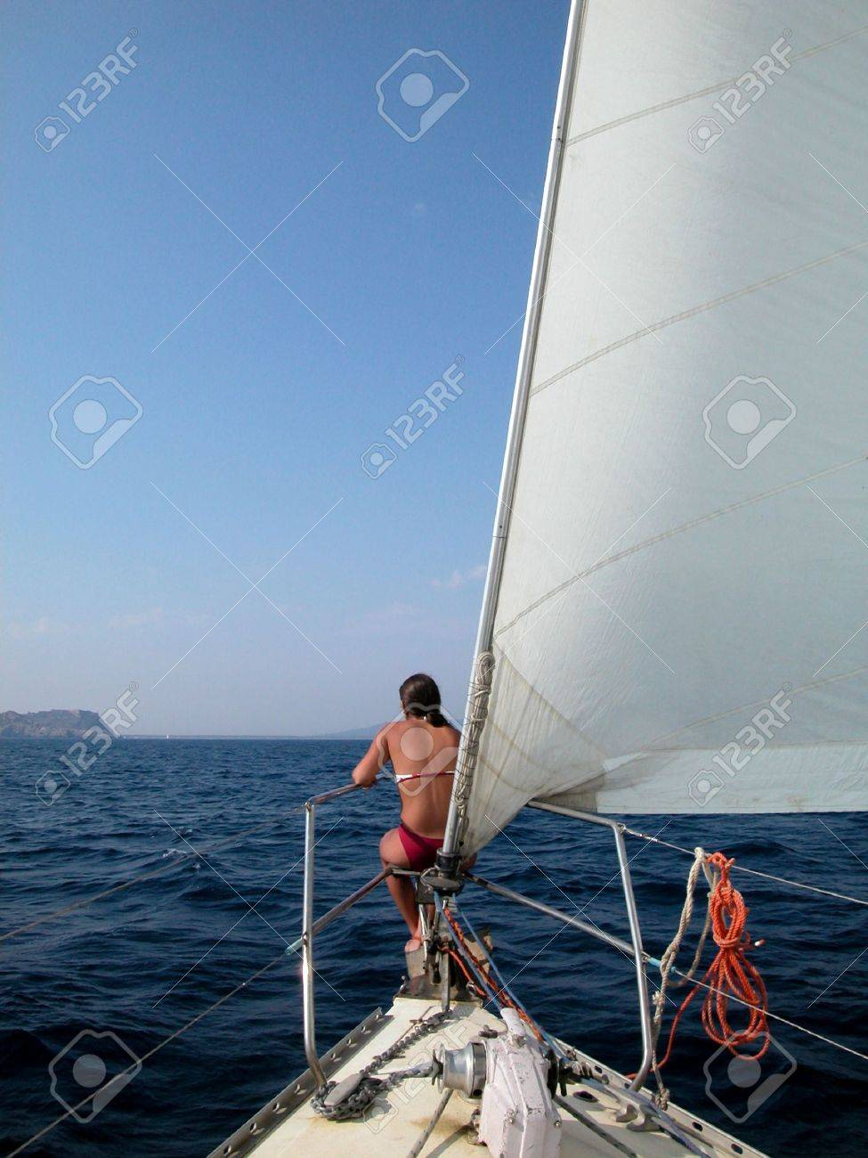 A woman sitting on the bow of the yacht looking at a beautiful sea view Stock Photo - 4935986