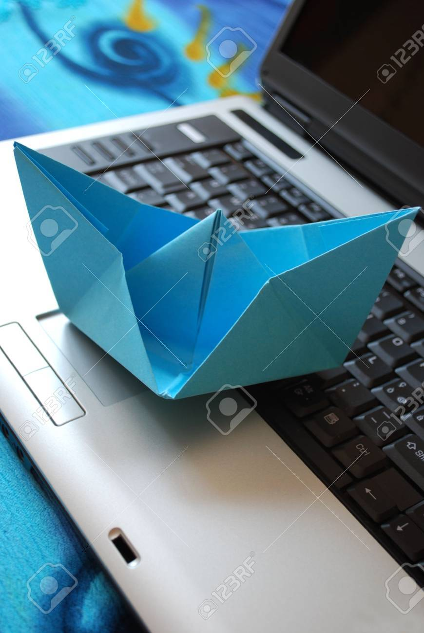 Blue paper boat sailing on laptop, vacation concept, internet surfing concept Stock Photo - 5148481
