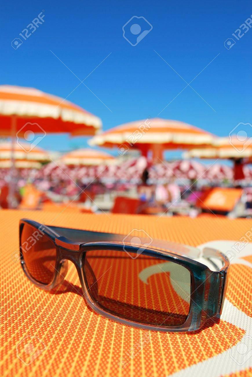 Closeup of sunglasses and beach with orange umbrellas in background, Rimini, Italy Stock Photo - 7642748