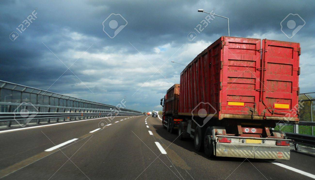 Red truck on highway under cloudy sky Stock Photo - 8343712