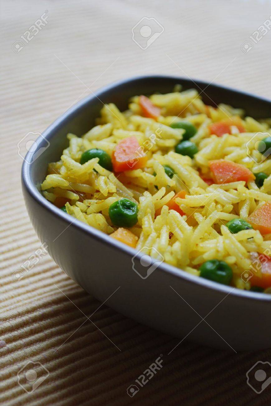 A bowl of yellow basmati rice with carrots, peas, onion and curry Stock Photo - 12516960