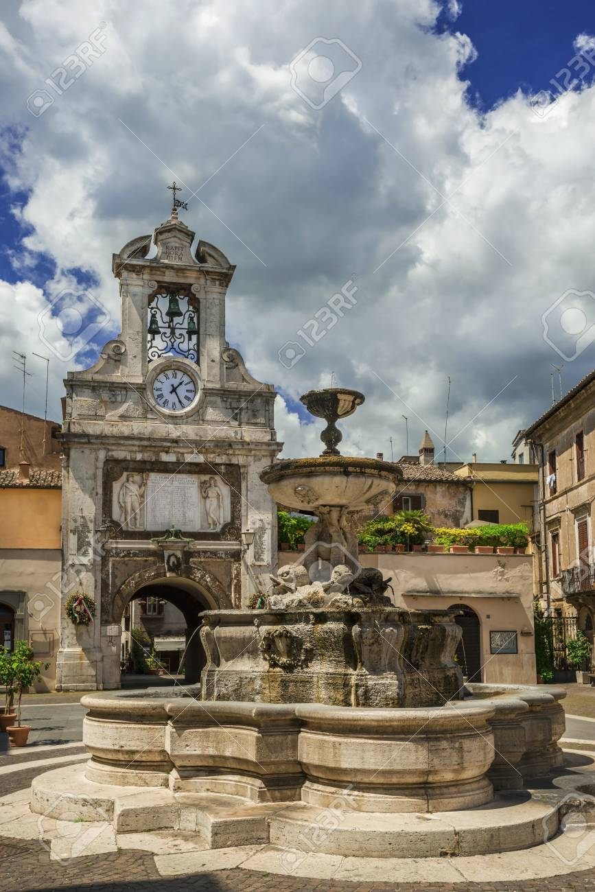 Sutri main square in the historic city center with fountain, old clock tower and clouds Banque d'images - 82471282