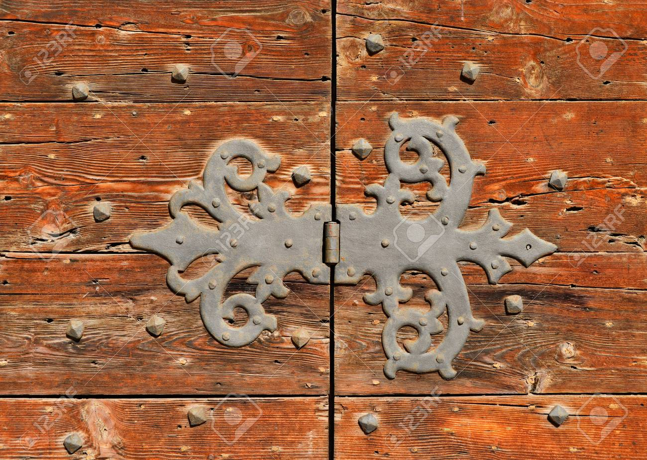 Old iron hinge on a worn wooden door Banque d'images - 82670487