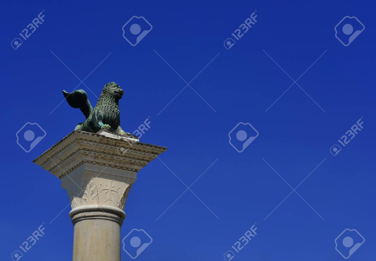 Saint Mark Lion ancient bronze statue at the top of the medieval column, erected in 1172. Symbol of the old Republic of Venice (with blue sky and copy space) Banque d'images - 82823485