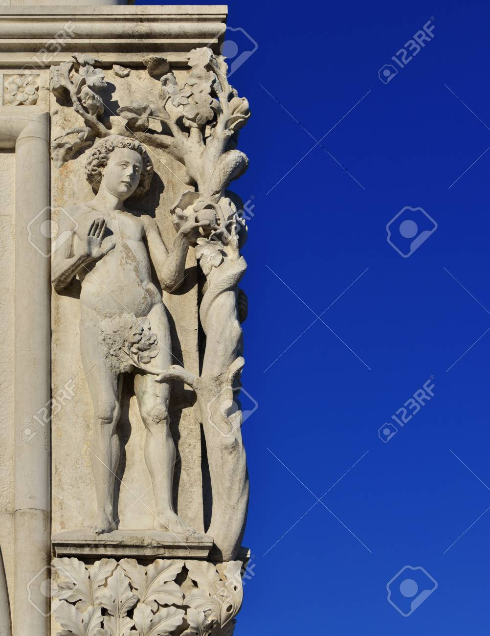 Adam the fist human in the Garden of Eden and the Original Sin, a medieval sculpture in Saint Mark Square, Venice (with copy space) Banque d'images - 84961990