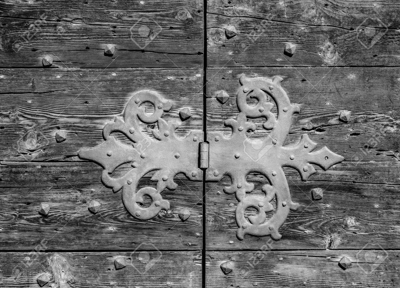 Old iron hinge on a worn wooden door (Black and White) Banque d'images - 84961991