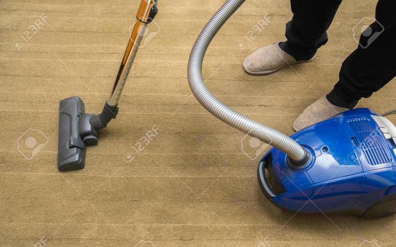 Dark head of a modern vacuum cleaner being used while vacuuming