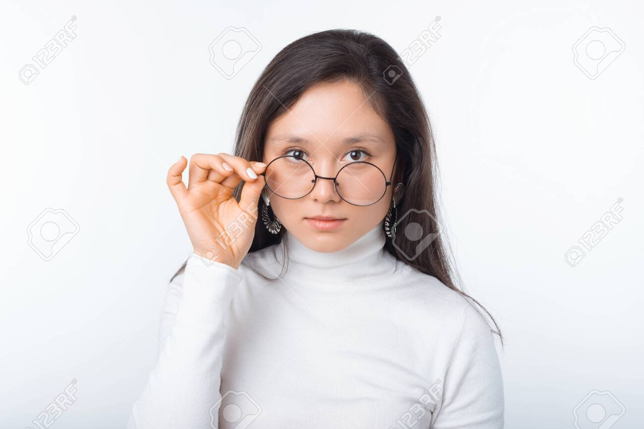 portrait of beautiful young woman wearing round glasses and looking confident at the camera - 144359965