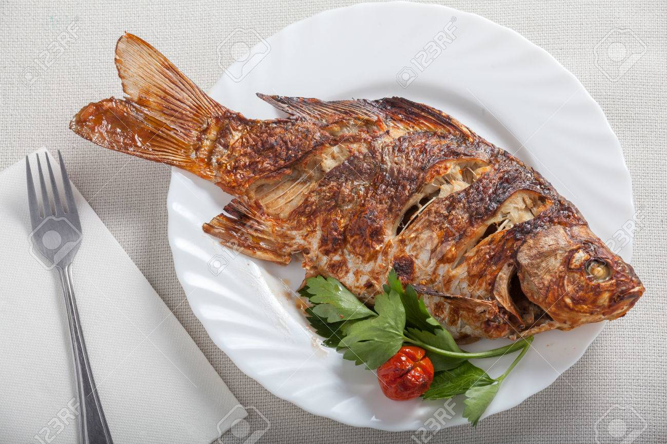 crisp carp fish cooked in the oven in the plate on the table stock